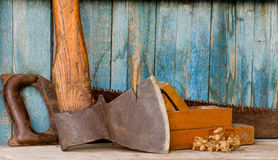 Carpenter tools: ax, planer and saw on the background of the old wooden walls.  Royalty Free Stock Image