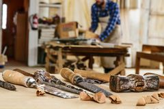 Carpenter tools. Chisel or gouge for wood on carpenter working at workbench. Carpentry workshop. Carpenter working with hammer and chisel on wood table. Workshop stock images