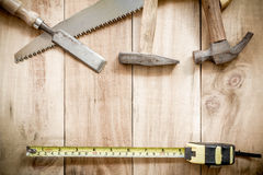 Carpenter tools,hammer,meter,nails, and chisel on wooden background. Royalty Free Stock Photos