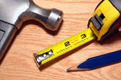 Carpenter Tools Hammer and Tape Measure on Wood stock photography
