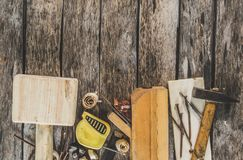 The carpenter tools on wooden bench, plane, chisel,mallet, tape measure, hammer, tongs, pliers, level, nails and a saw. The carpenter tools on wooden bench Royalty Free Stock Photos