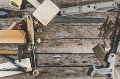 The carpenter tools on wooden bench, plane, chisel,mallet, tape measure, hammer, tongs, pliers, level, nails and a saw. The carpenter tools on wooden bench Royalty Free Stock Image