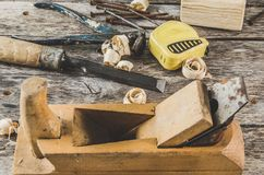 The carpenter tools on wooden bench, plane, chisel,mallet, tape measure, hammer, tongs, pliers, level, nails and a saw. The carpenter tools on wooden bench Royalty Free Stock Photo