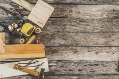 The carpenter tools on wooden bench, plane, chisel,mallet, tape measure, hammer, tongs, pliers, level, nails and a saw. The carpenter tools on wooden bench Stock Image