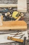 The carpenter tools on wooden bench, plane, chisel,mallet, tape measure, hammer, tongs, pliers, level, nails and a saw. The carpenter tools on wooden bench Royalty Free Stock Photography