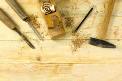 Carpenter tools on wooden table with sawdust. Craftperson workplace top view.  Royalty Free Stock Images