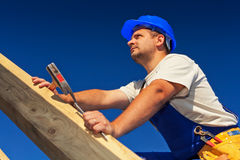 Carpenter on top of roof structure. Inspecting the building Stock Photo