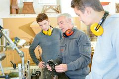 Carpenter trainees learning with boss about machinery. Worker stock photo