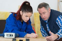 Carpenter training female apprentice to use plane. Appretice stock photography