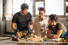 Carpenter Training Female Apprentice To Use Plane. Group of students in woodwork training course Stock Photography