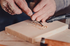 Carpenter use a chisel to shapes a wooden plank. Royalty Free Stock Photos