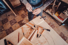 Carpenter use a chisel to shapes a wooden plank. Stock Photos