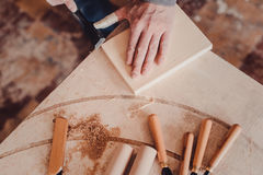Carpenter use a chisel to shapes a wooden plank. Stock Image
