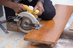 Carpenter use electric saw to sawing wood Royalty Free Stock Photo