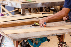 Carpenter use saw cut wood for make new furniture Royalty Free Stock Photo