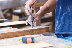 Carpenter use saw cut wood for make new furniture Stock Image