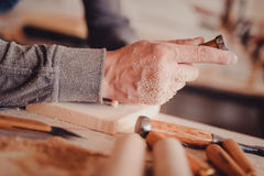 Carpenter use a chisel to shapes a wooden plank. Stock Photography