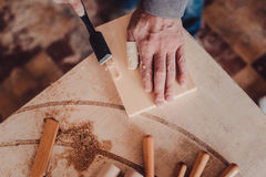 Carpenter use a chisel to shapes a wooden plank. Royalty Free Stock Images