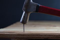 The carpenter uses a hammer to hit the nail Stock Image