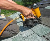 Carpenter uses nail gun to attach asphalt shingles