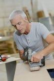 Carpenter using belt sander Stock Images