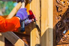 Carpenter is using chisel and hammer to groove vertical line. Close up hands of carpenter with chisel and hammer during grooving w. Ork Royalty Free Stock Photo