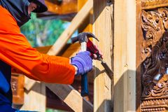 Carpenter is using chisel and hammer to groove vertical line. Close up hands of carpenter with chisel and hammer during grooving w. Ork Stock Photo
