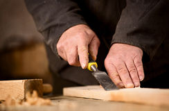 Carpenter using a chisel on a plank of wood. To shape and cut a groove as he manufactures an article in his woodworking workshop, view of the hands and chisel Royalty Free Stock Images
