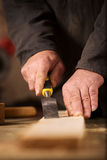 Carpenter using a chisel on a plank of wood Royalty Free Stock Photos