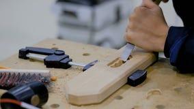 Carpenter using chisel to carve wood. Professional man carpenter using chisel to carve wood on rough workbench at workshop. Design, carpentry, craftsmanship and stock video