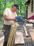 Carpenter using chop saw. Carpenter cutting balusters for a deck railing with a chop saw royalty free stock photos