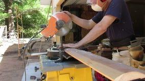 A Carpenter using a Chop Saw. A man cuts a board using a power miter saw stock video