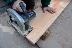 Carpenter Using Circular Saw. A carpenter trims a plank using a circular saw Stock Image