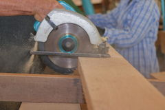 Carpenter using circular saw cutting wooden board in wood workshop. Carpenter using circular saw cutting wooden board in wood workshop Stock Photos
