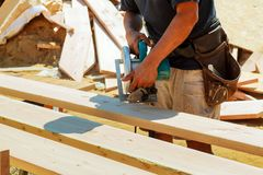 Carpenter using circular saw for cutting wooden boards. Construction details of male worker or handy man. With power tools Stock Photography