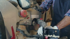 Carpenter using a circular saw to cut a large board of wood in workshop. stock video