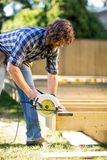 Carpenter Using Circular Saw. To cut plank while building a deck Stock Photography
