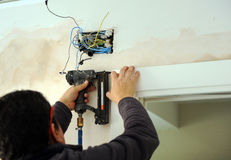Carpenter using a compressed air nailer to insert nails in the assembly of a sliding door Royalty Free Stock Photography