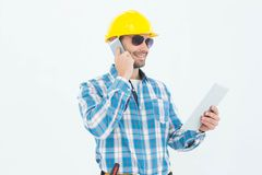 Carpenter using digital tablet and cellphone Stock Photography