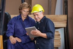 Carpenter Using Digital Tablet With Colleague. Senior carpenter using digital tablet with colleague in workshop Royalty Free Stock Photos
