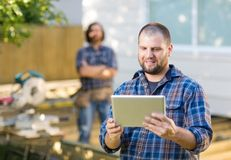 Carpenter Using Digital Tablet With Coworker Royalty Free Stock Photography