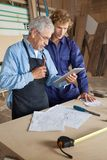 Carpenter Using Digital Tablet With Coworker. Senior carpenter using digital tablet with coworker in workshop Royalty Free Stock Photo