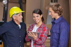 Carpenter Using Digital Tablet With Coworkers Royalty Free Stock Photo