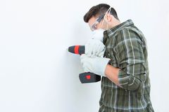 Carpenter using drill machine on white wall Royalty Free Stock Photo