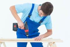Carpenter using drill machine on wood Stock Image