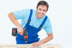 Carpenter using drill machine on wood Stock Photo