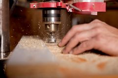 Carpenter using drill press to mae hole in wooden plank. Carpenter in the workshop, drill in hand Royalty Free Stock Photos