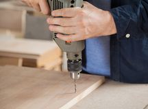 Carpenter Using Drill On Wood In Workshop Royalty Free Stock Image