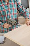 Carpenter Using Electric Drill In Workshop Stock Photo