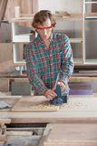 Carpenter Using Electric Planer On Wood. Mid adult carpenter using electric planer on wood at workshop Stock Image